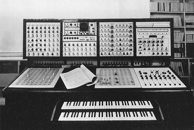 An image of the Synthi 100 modular analog synthesizer. On the front we see the two keyboards and the sides that looks like a score, the two panels to create patches for the modules.