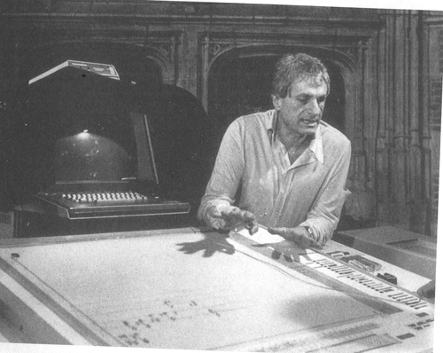Iannis Xenakis engaged in a demonstration of the UPIC system. Under the hands of the composer you notice digital board, interfaced with the computer behind him.
