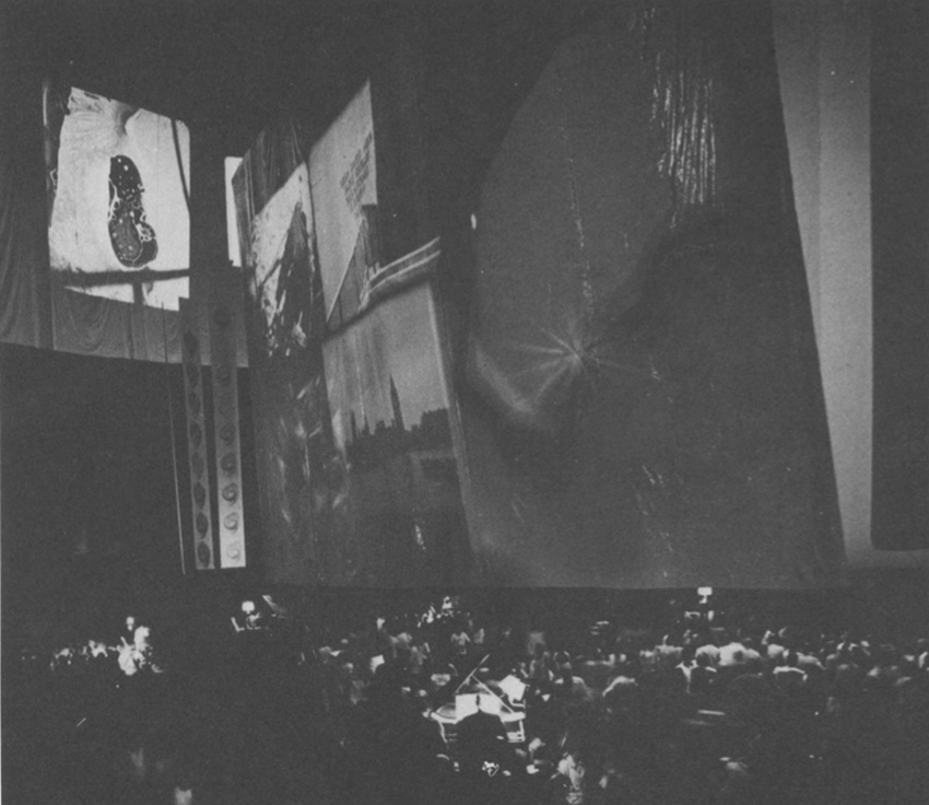 A picture of the performance of May 16, 1969. Do you see the center of the performers and around the banners and graphics for image projections.